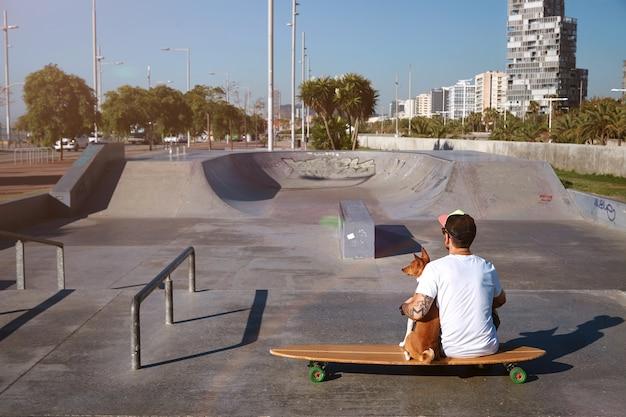Surfista sentado em um longboard em um skatepark da cidade abraçando seu cachorro basenji marrom e branco, olhando a paisagem da cidade, filmado de costas
