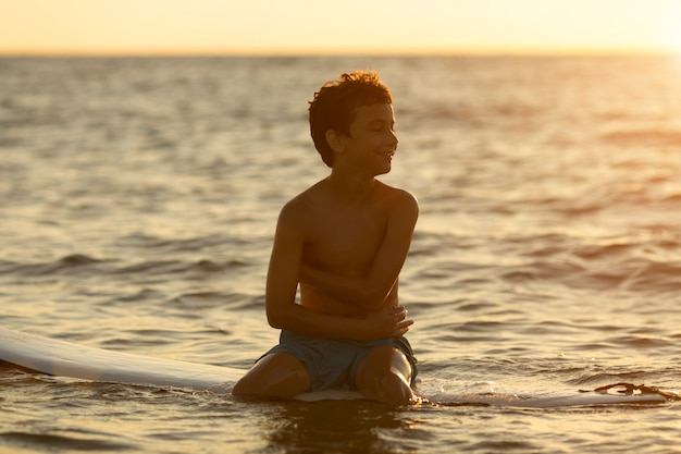 Surfista sentado em uma prancha de surf ao amanhecer