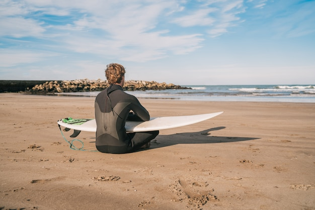 Surfista sentado na praia com prancha de surf