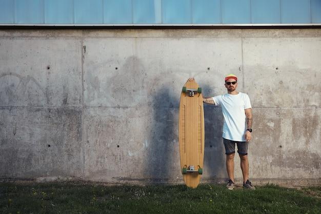 Surfista sério com barba, tatuagens e óculos escuros ao lado de seu longboard