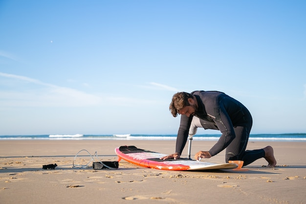Surfista sério com roupa de neoprene usando membro artificial, prancha de cera na areia na praia do oceano