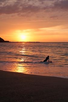 Surfista subindo em sua prancha ao pôr do sol