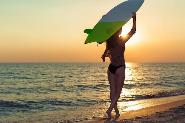 Surfista surfando no pôr do sol na praia do oceano
