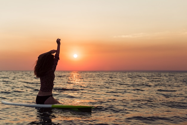 Surfista surfando olhando para o pôr do sol praia do oceano