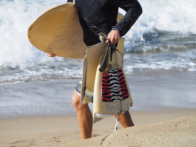 Surfista vai ao longo da praia com uma prancha quebrada.
