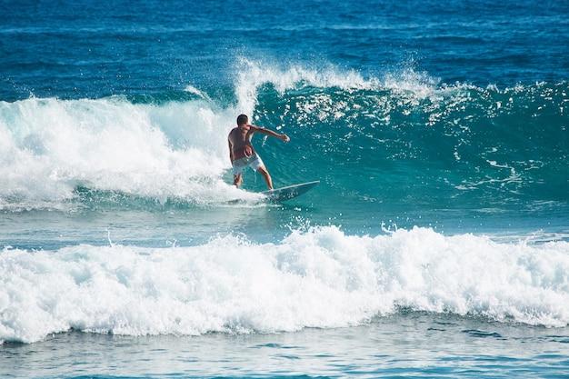 Surfista vestido com shorts de prancha cavalga em alta velocidade em uma onda.