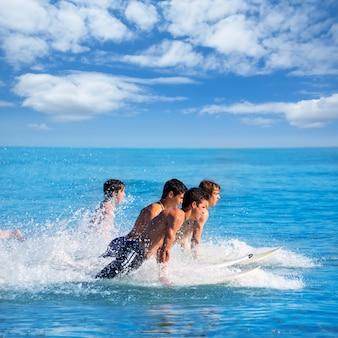 Surfistas de rapazes surfando correndo pulando em pranchas de surf