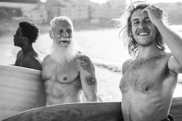 Surfistas de várias gerações se divertindo na praia - concentre-se no rosto do homem certo