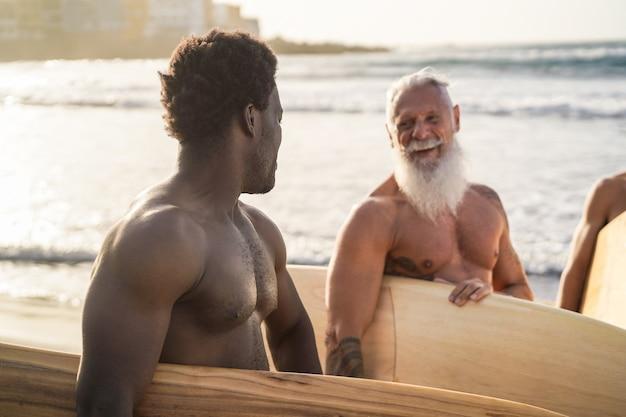 Surfistas de várias gerações se divertindo na praia - foco no homem africano