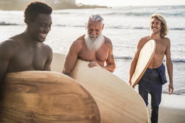 Surfistas de várias gerações se divertindo na praia - foco principal no rosto de idosos