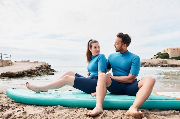 Surfistas felizes sentados em prancha de remo na praia