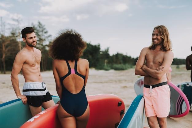 Surfistas masculinos e fêmeas que falam na praia.