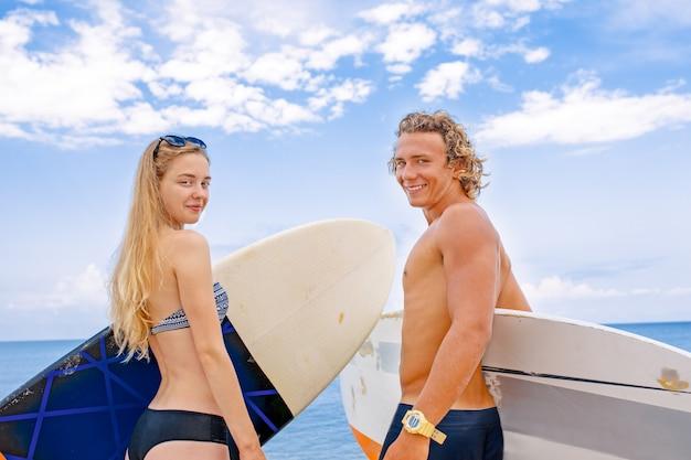 Surfistas na praia - sorrindo casal de surfistas caminhando na praia e se divertindo no verão. esporte radical e conceito de férias