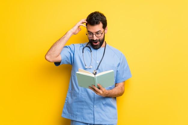 Surgeon médico homem surpreendido enquanto desfruta de ler um livro