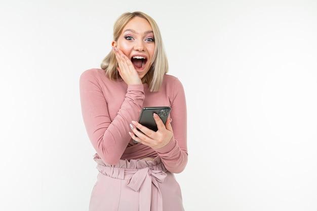 Surpreenda a garota feliz em roupas cor de rosa, navegar na internet no telefone em um fundo branco
