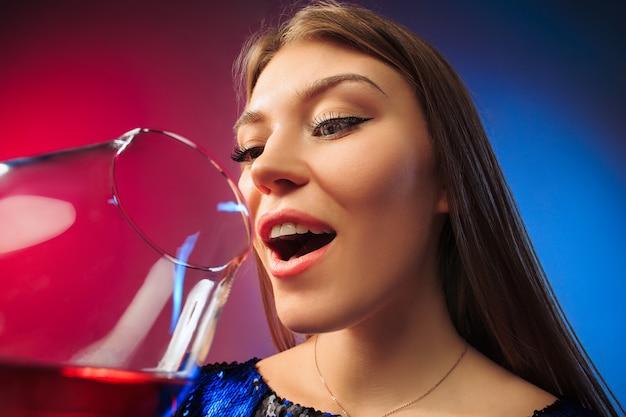 Surpreendeu a jovem com roupas de festa, posando com um copo de vinho. rosto fofo feminino emocional.