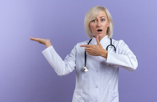 Surpreendeu a médica adulta com manto médico com estetoscópio apontando para a mão dela isolada na parede roxa com espaço de cópia