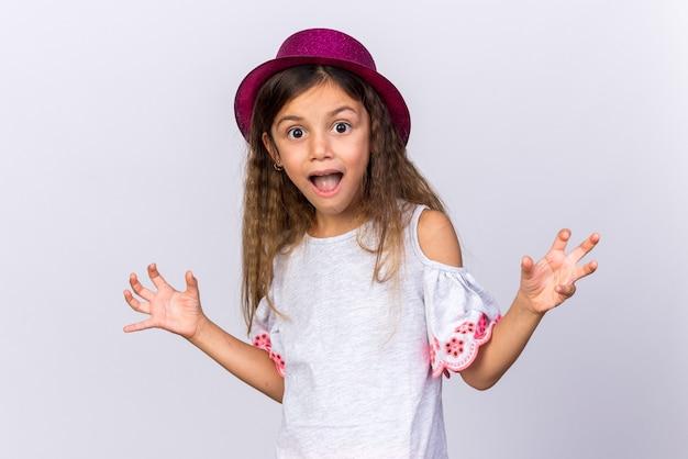 Surpreendeu a menina caucasiana com chapéu de festa roxo, mantendo as mãos abertas, isolado na parede branca com espaço de cópia