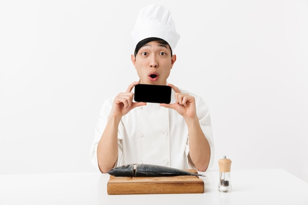Surpreendeu o chefe japonês com uniforme de cozinheiro branco segurando um smartphone enquanto filé de peixe fresco cru isolado sobre a parede branca
