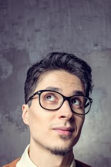 Surpreendeu o homem feliz usando óculos, olhando para cima perto retrato
