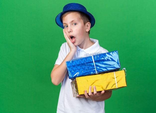 Surpreendeu o jovem eslavo com chapéu de festa azul, colocando a mão no rosto e segurando caixas de presente isoladas na parede verde com espaço de cópia