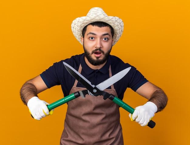 Surpreendeu o jovem jardineiro caucasiano usando luvas e chapéu de jardinagem, segurando uma tesoura de jardinagem e parecendo isolado em uma parede laranja com espaço de cópia