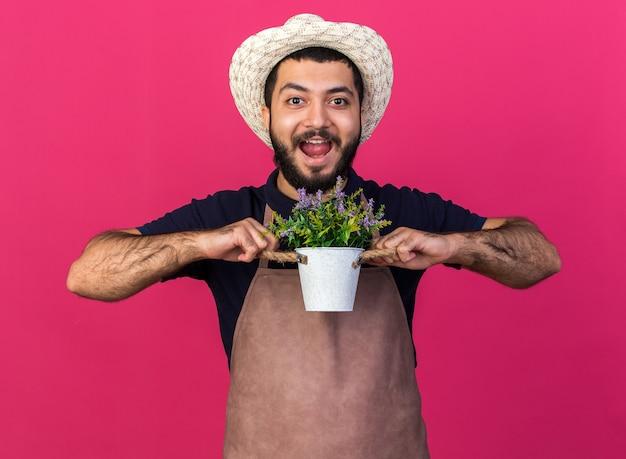 Surpreendeu um jovem jardineiro caucasiano usando um chapéu de jardinagem segurando um vaso de flores isolado na parede rosa com espaço de cópia