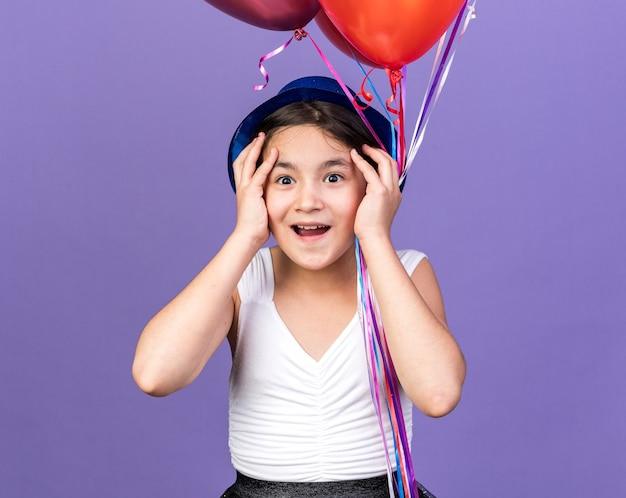 Surpreendeu uma jovem caucasiana com chapéu de festa azul, colocando as mãos no rosto, segurando balões de hélio isolados na parede roxa com espaço de cópia