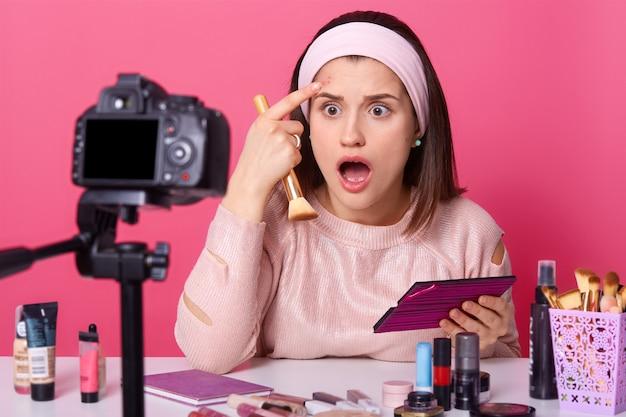 Surpreendida blogueira se pergunta e atordoada ao perceber acne na testa, segura escova cosmética e olha para a câmera