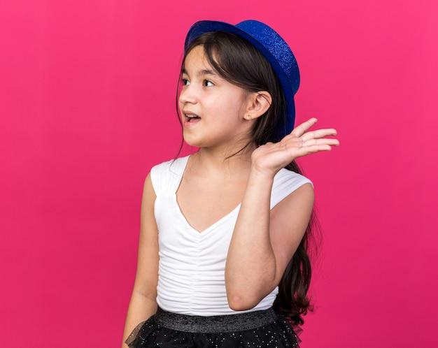 Surpreendida jovem caucasiana com chapéu de festa azul em pé com a mão levantada olhando para o lado isolado na parede rosa com espaço de cópia
