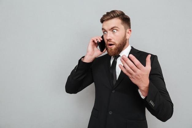 Surpreendido homem barbudo falando no telefone e olhando para longe