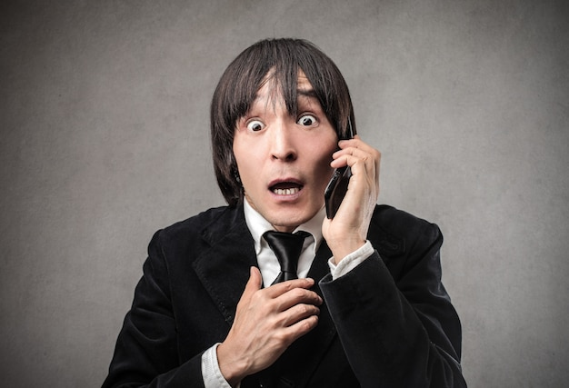 Surpreendido homem japonês falando ao telefone