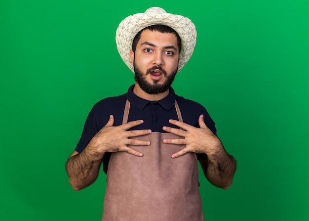 Surpreendido, jovem jardineiro caucasiano com chapéu de jardinagem coloca as mãos no peito isolado em parede verde com espaço de cópia