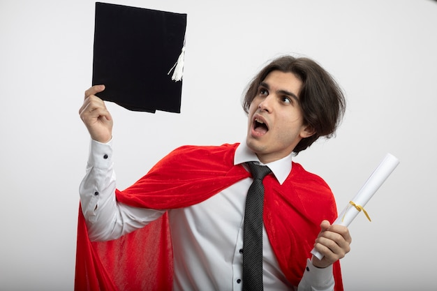 Surpreendido, jovem super-herói, usando gravata, segurando um diploma e olhando para um chapéu de pós-graduação na mão, isolado no fundo branco