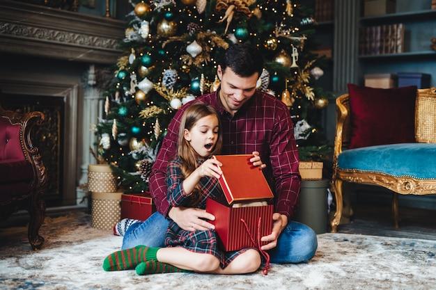 Surpresa adorável menina pequena olha para a caixa de presente, não acredita em seus olhos, recebe presente agradável do pai