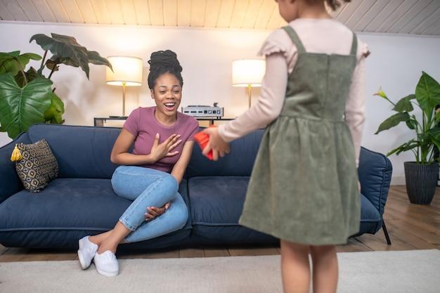 Surpresa agradável. filha de pele escura em pé de costas para a câmera com uma caixa vermelha para uma jovem mãe alegre sentada no sofá em casa