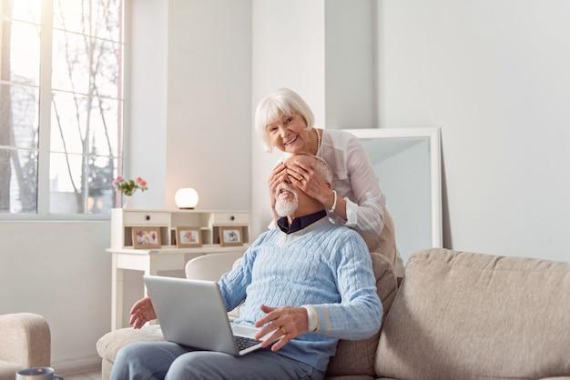 Surpresa agradável. mulher idosa encantadora e otimista surpreendendo o marido ao cobrir os olhos dele por trás enquanto ele trabalhava no laptop