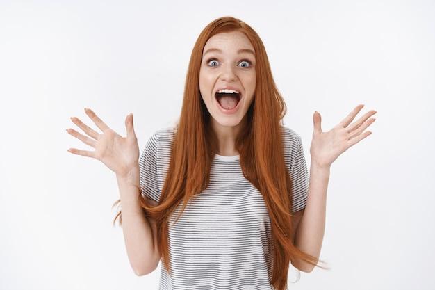 Surpresa animada ruiva emocionada entusiasmada ruiva jovem gritando emocionada levantando as mãos arregalar os olhos impressionado receba notícias fantásticas bons resultados finalmente atingir o objetivo, parede branca