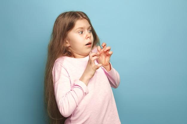 Surpresa assustada menina adolescente em um fundo azul do estúdio. expressões faciais e conceito de emoções de pessoas.
