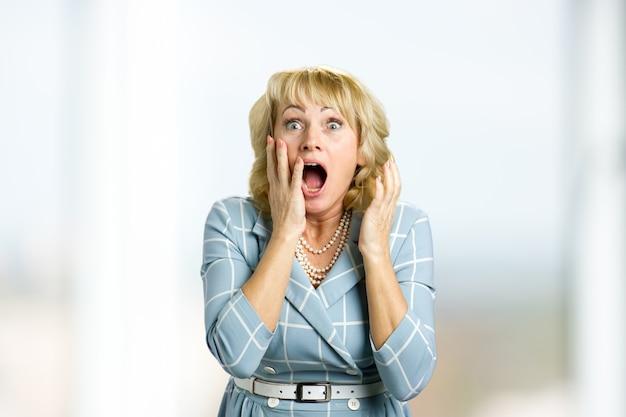 Surpresa atônita mulher de meia-idade. feche o retrato de uma mulher parecendo surpresa em total descrença, com a boca aberta e as mãos levantadas.