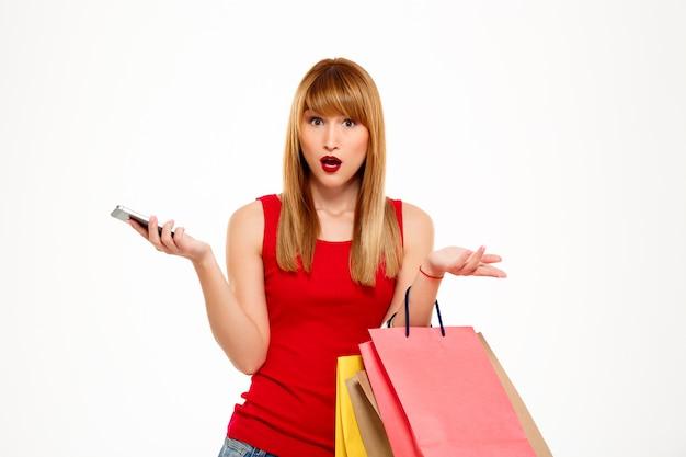 Surpresa bela jovem de pé com as compras sobre parede branca