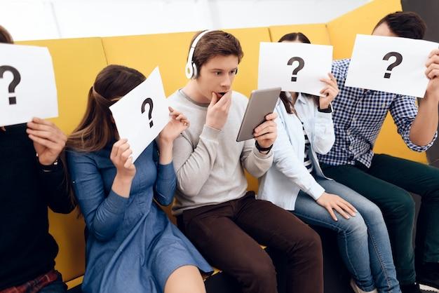 Surpresa cara jovem em fones de ouvido olha para tablet