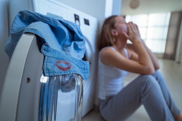 Surpresa chateada estressada mulher chora encontrada no colarinho da camisa do marido marcas de batom vermelho feminino enquanto lavanderia