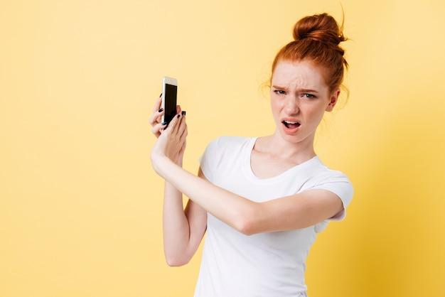 Surpresa chateada mulher gengibre em t-shirt cobrindo smartphone nas mãos
