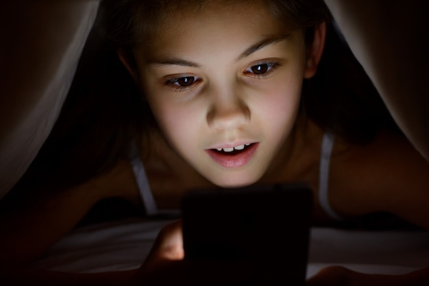 Surpresa chocada criança do sexo feminino olhando para o celular debaixo do cobertor à noite. menina pequena é surpreendida jogando jogos em seu smartphone