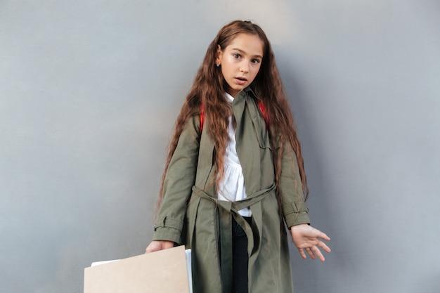 Surpresa colegial morena com cabelos longos, vestido com roupas quentes