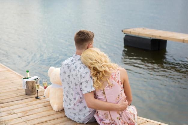 Surpresa de encontro romântico. um rapaz e uma garota em um píer de madeira. abraço e beijo enquanto está sentado no píer. história de amor romântica