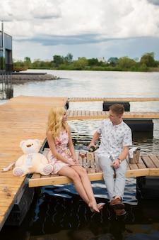 Surpresa de encontro romântico. um rapaz e uma garota em um píer de madeira. o cara derrama champanhe nos copos.