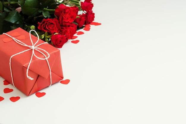 Surpresa de férias românticas. caixa de presente e rosas vermelhas em branco