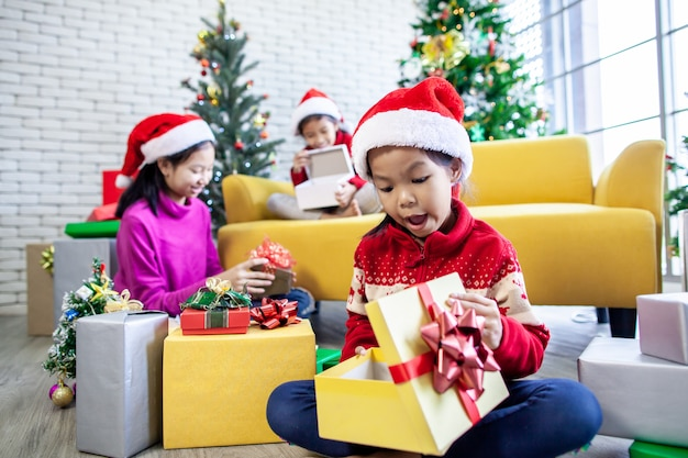 Surpresa de garotas asiáticas com presente e ajudando a decorar juntos para comemorar no festival de natal
